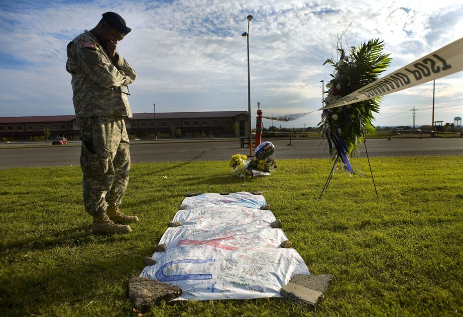 Sgt. 1st Class Noval Alexander reads some of the condolences left by a local high school at a makeshift memorial for the victim's of the Fort Hood massacre.