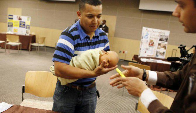 """Miguel Cano aprende la manera correcta de sostener a un bebé durante el taller """"Celebrando a los padres"""", que efectuó recientemente el sistema de salud del hospital Parkland de Dallas. (Special Contributor/BEN TORRES)"""