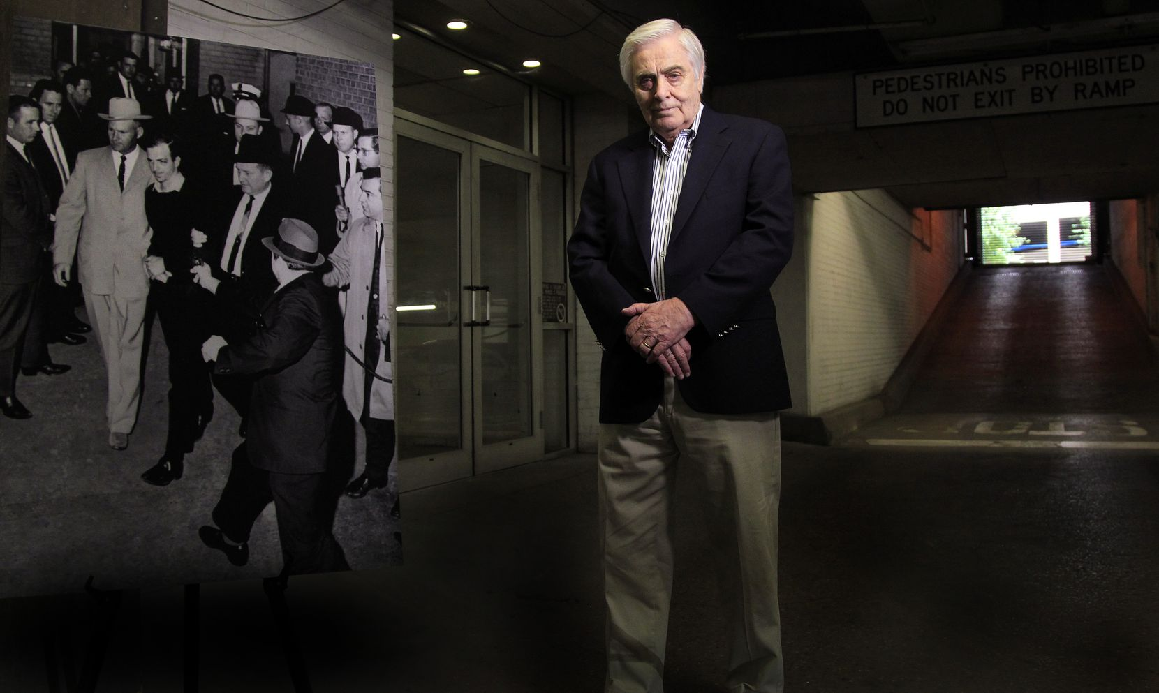 A 2013 photo of Hugh Aynesworth, former Dallas Morning New reporter and author of many books, near a photograph of Jack Ruby shooting and killing Lee Harvey Oswald (taken by Jack Beers of The Dallas Morning News) in the garage of the Dallas Police station. Hugh was about 40 feet away when he witnessed the event on November 24, 1963.