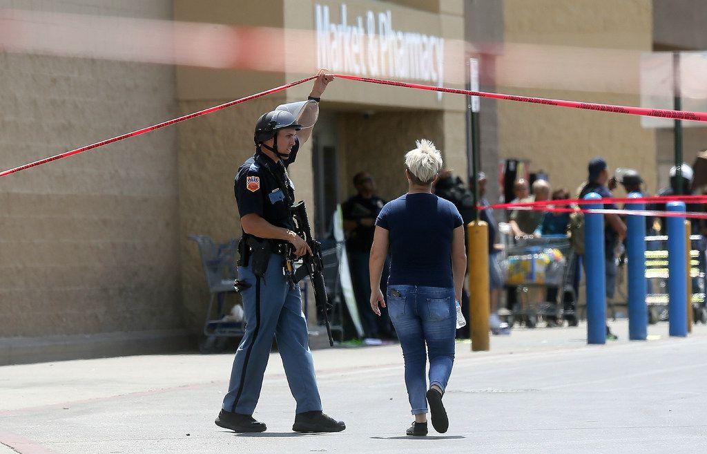 An employee crosses into the crime scene following a shooting at a Walmart in El Paso, Texas, Saturday, Aug. 3, 2019. (Mark Lambie/The El Paso Times via AP)