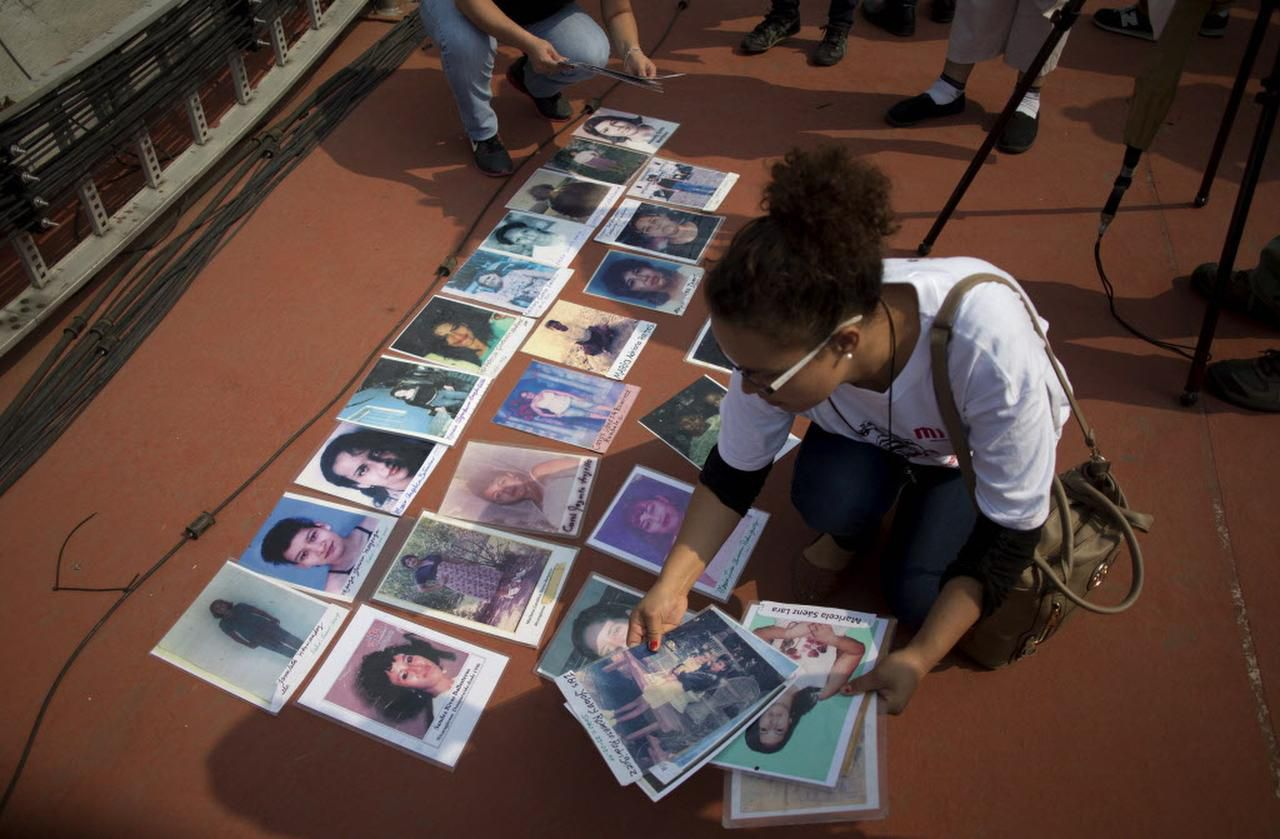 Una mujer coloca fotos de migrantes centroamericanos durante una marca de madres que buscan sus hijos, el 9 de diciembre en la Ciudad de México.A woman lays pictures of missing Central American migrants during a march by mothers who are searching for their children, in Mexico City, Wednesday, Dec. 9, 2015. The caravan of women, mostly from Central America, are traveling through Mexico to search for their relatives who left for a better life in the U.S. but disappeared. (AP Photo/Eduardo Verdugo) (AP/Eduardo Verdugo)