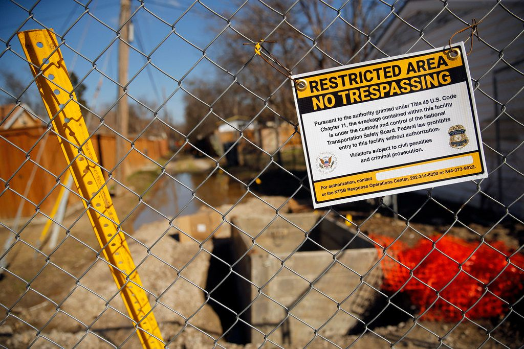 A National Transportation Safety Board sign on Friday warned people to stay out of the alley behind a home on Espanola Drive where a home exploded last week, killing 12-year-old Linda Rogers. Crews are digging up the surrounding neighborhood to replace natural gas lines in northwest Dallas.