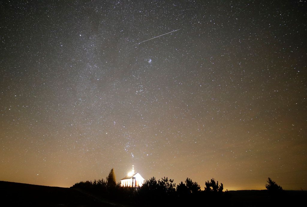 A meteor streaks across the sky during the annual Geminids meteor shower over an Orthodox church on the local cemetery near the village of Zagorie,Belarus, late Wednesday.