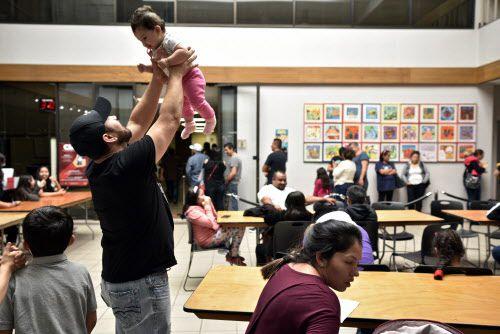 Wilson Díaz, de 35 años, juega con su hija, durante un taller en el que se explicó cómo hacer cartas de poder para dejar a menores en manos de guardianes legales.