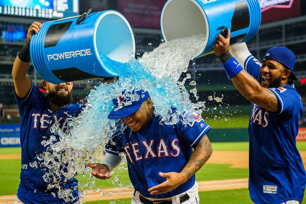Texas Rangers left fielder Willie Calhoun is doused by second baseman Rougned Odor (12) and shortstop Elvis Andrus (1) after the Rangers 9-7 victory over the Seattle Mariners at Globe Life Park on Wednesday, July 31, 2019, in Arlington. (Smiley N. Pool/The Dallas Morning News)