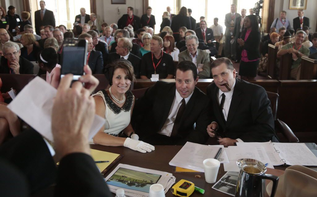 Shelley Shook, left,  and her husband Toby Shook, who plays Lee Harvey Oswald's attorney, pose with Cameron Cox, who portrayed Lee Harvey Oswald, center,  during a mock trial for Lee Harvey Oswald in the assassination of JFK at the old criminal courts building in Dallas, Texas on June 21, 2013.