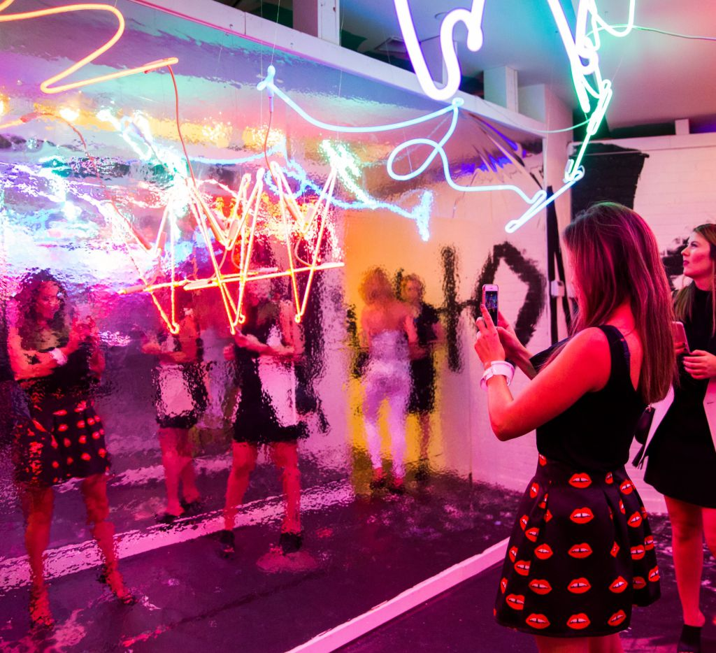 Visitors to a pop-up art installation take selfies.