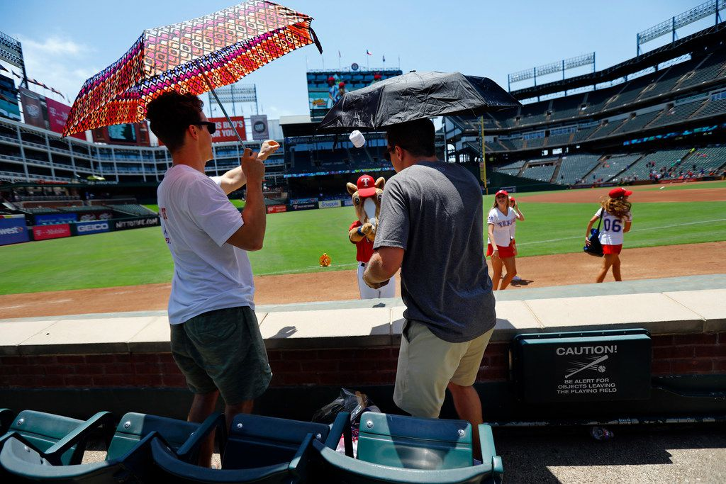 Texas Rangers fans Tom Hamilton of Plano (left) and Peter Brown of Knoxville, Tenn., catch a T-shirt tossed by Rangers Captain before the start of Sunday's game against Cleveland at Globe Life Park in Arlington. Few fans braved the heat for the game, which started at 2:05 p.m. on a day when temperatures were expected to approach 110 degrees