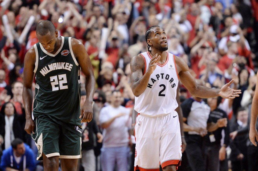 Toronto Raptors forward Kawhi Leonard (2) reacts as Milwaukee Bucks forward Khris Middleton (22) looks on following the Raptors win Game 3 of the NBA basketball playoffs Eastern Conference finals in Toronto on Sunday, May 19, 2019. (Nathan Denette/The Canadian Press via AP)