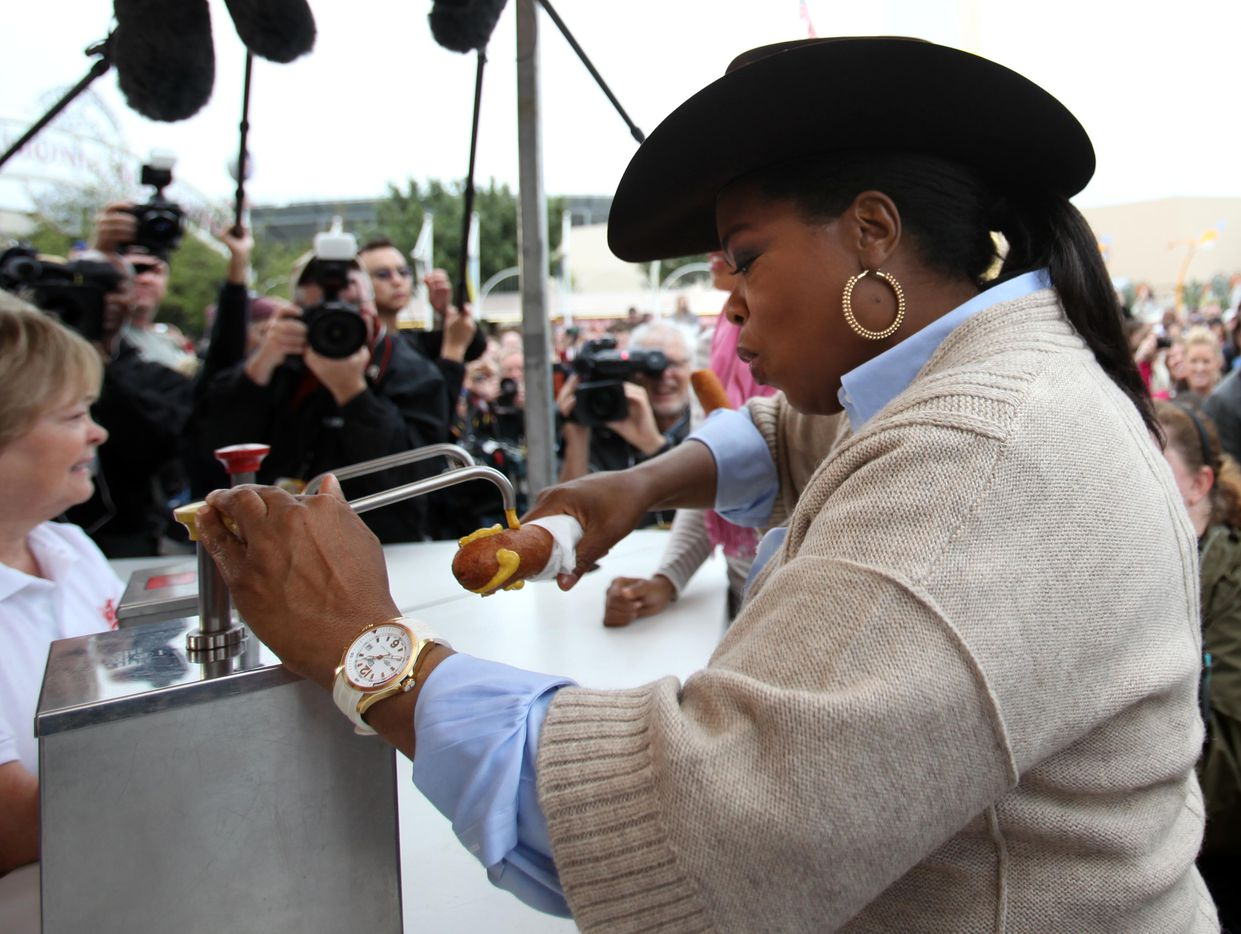Oprah Winfrey applies mustard to her corny dog at the State Fair of Texas in Dallas on Sunday, October 11, 2009.