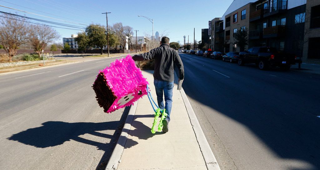 Dallas artist Giovanni Valderas places one of the pieces of his project called Casitas Tristas on Fort Worth Drive in Dallas on Jan. 14, 2018.  He creates small houises in protest of the lack of affordable housing in Oak Cliff, the neighborhood he grew up in. (Nathan Hunsinger/The Dallas Morning News)