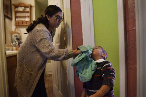 Madai Ochoa, de 17 años ayuda a su hijo Ethan a limpiarse su cara. BEN TORRES/DMN