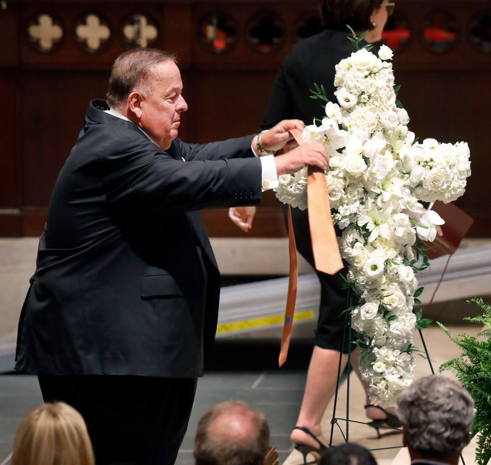 At the conclusion of his speech, longtime friend Alan White took off his Oklahoma State-colored tie and draped it across a white floral bouquet during the funeral service for T. Boone Pickens at Highland Park United Methodist Church.