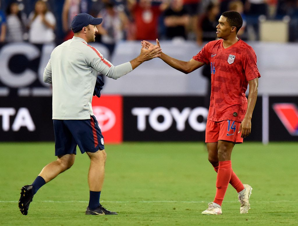 United States midfielder Reggie Cannon (14) is congratulated after the team's win against Jamaica in an CONCACAF Gold Cup semifinal soccer match Wednesday, July 3, 2019, in Nashville, Tenn. The United States won 3-1. (AP Photo/Mark Zaleski)