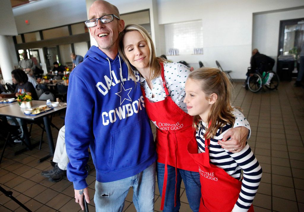 Meredith Land gives Reid Holiday, who is hearing impaired, a hug after serving lunch with daughter McCall and family at Salvation Army's Carr P. Collins Social Service Center  in Dallas.
