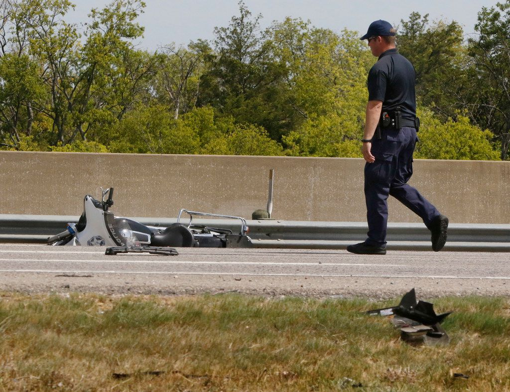 """An accident investigator collected evidence Saturday at the crash scene where Dallas police Senior Cpl. Earl """"Jamie"""" Givens was struck and killed. (Irwin Thompson/Staff Photographer)"""