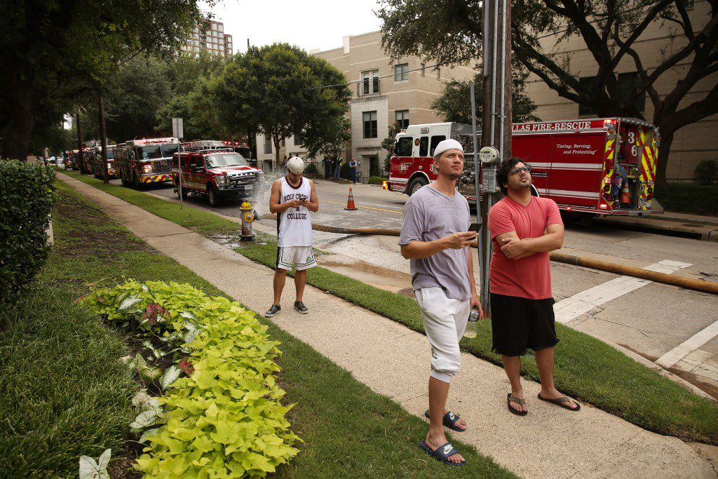 Onlookers gathered outside an Uptown apartment complex  as Dallas Fire-Rescue put out a fire Wednesday.