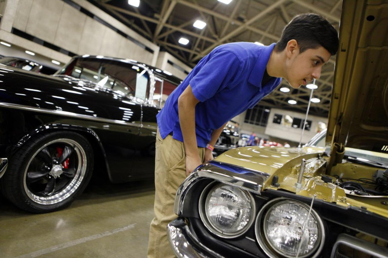 Estudiantes de mecánica automotriz de la preparatoria W.H. Adamson aprenden sobre autos antiguos en un paseo escolar a la subasta de Mecum en Dallas. (ARCHIVO AL DÍA/BEN TORRES)