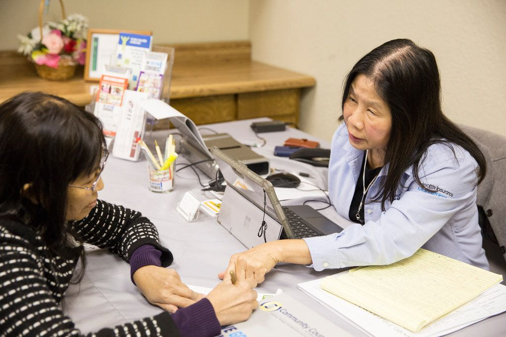 Lisa Pham (right) goes over insurance options with Mua Thi Nguyen at the Vietnamese community center in Pantego, Texas, on Nov. 8, 2017.
