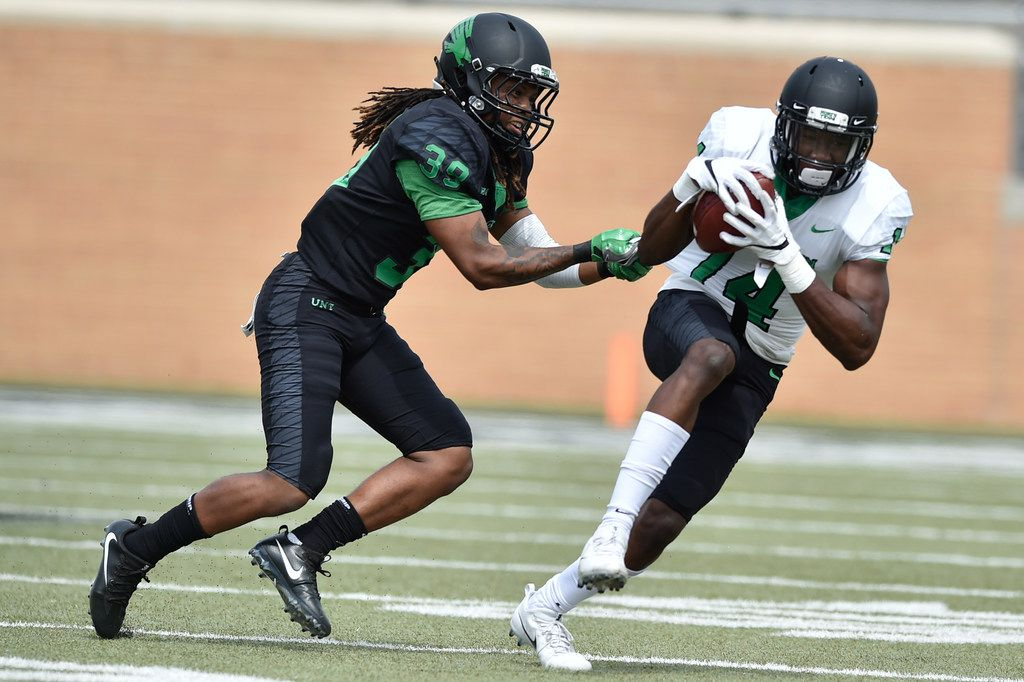 North Texas freshman wide receiver Greg White (14) catches a pass and is tackled by North Texas junior defensive back Jameel Moore (39) at Apogee Stadium, Saturday, March 24, 2018, in Denton, Texas, Jeff Woo/DRC