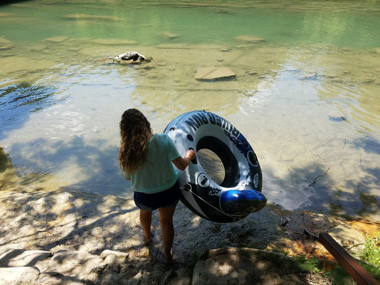 "Bellville mom Tracy Corum carries a tube marked in honor of her son, Justin Hernandez, to the bank of the Guadalupe River in New Braunfels, Texas, on July 16, 2017. She let the tube float empty with the message, ""if you find me, float me.""(Submitted photo/Tracy Corum)"