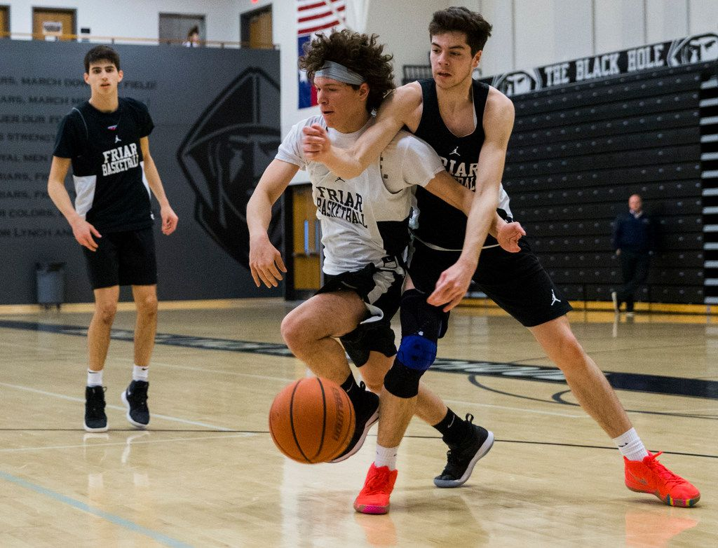 Bishop Lynch High School varsity basketball player Jarett Nunez, center, plays defends Jake Milkereit during practice on Thursday, January 24, 2019 at Bishop Lynch High School in Dallas. Nunez was born with a deformed left hand, but that didn't stop him from making the varsity basketball team, running track or playing football. (Ashley Landis/The Dallas Morning News)