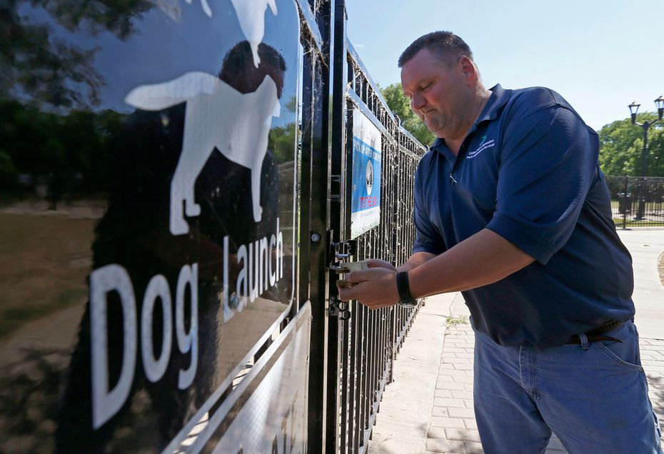 Russell Hooper of the Dallas Park & Recreation Department locks up the gate of the dog launch at White Rock Lake on June 28.