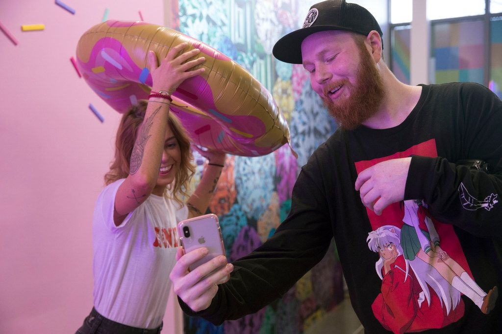 Fort Worth residents Tate Lee, right, and Riley Shapter review a picture inside Snap 151, a pop-up installation, in Fort Worth, Texas on Thursday, January 17, 2019. (Daniel Carde/The Dallas Morning News)