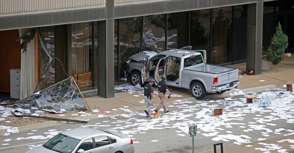 Police officers walked through the debris in front of the station after a pickup driver crashed intentionally into the KDFW-TV (Channel 4) studios in downtown Dallas on Sept. 5.