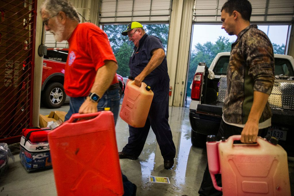 Volunteers move cans of gasoline inside Lumberton Central Fire Station as Hurricane Harvey hit landfall for a second time on Tuesday, August 29, 2017 in Lumberton, Texas. (Ashley Landis/The Dallas Morning News)
