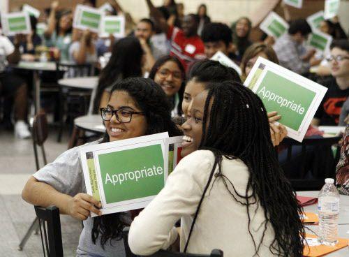 Giovanna Chávez (izq.) y Mary Obanor muestran sus carteles de aprobación durante el desfile de modas para los estudiantes. BEN TORRES/AL DÍA