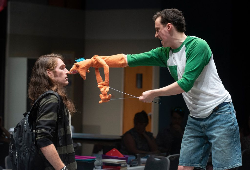 """Garret Storms (Timothy), left, and Parker Gray (Jason), challenging Timothy with Jason's puppet, Tyrone, in the regional premiere """"Hand to God"""" at the Water Tower Theatre at Addison Theatre Centre."""
