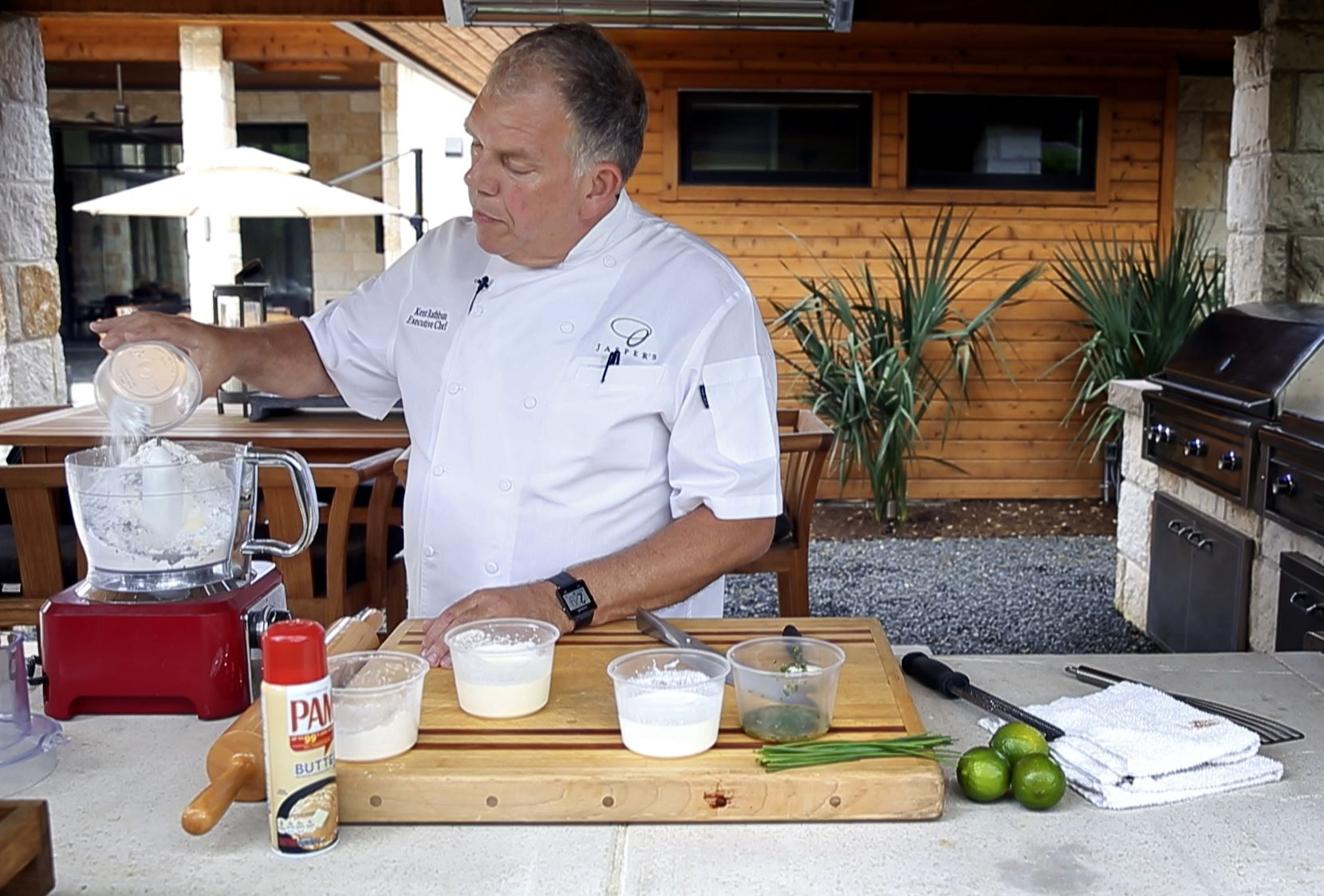Chef Ken Rathbun dumps flour into a food processor as he makes ancho chili-lime biscuits at his home.