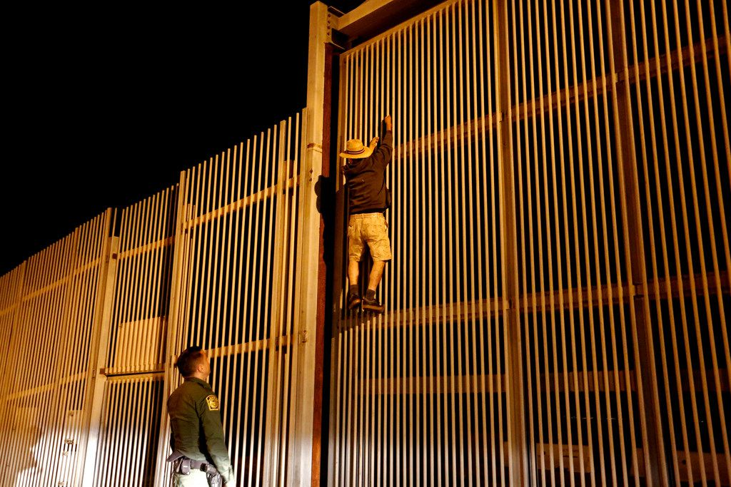 Border Patrol agent Eduardo Olmos apprehends a Mexican immigrant trying to climb the secondary fence into Border Field State Park in San Diego, Calif. from Playas de Tijuana.