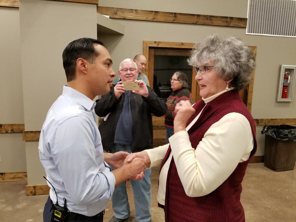 Julián Castro, campaigning for president in Exira, in Iowa's Audubon County, on Feb. 21, 2019, speaks with Andrea Crane as her husband, Gene Crane, takes a photo.