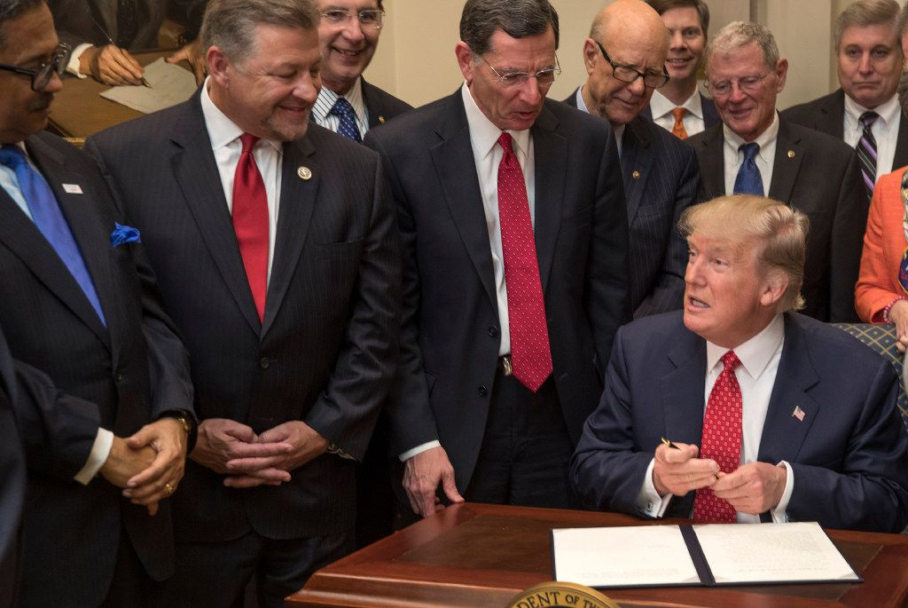 FILE -- President Donald Trump signs back-to-back executive orders in the White House in Washington, Feb. 28, 2017. In its first month and a half, the Trump administration has already suspended or reversed more than 90 regulations, sounding the alarm about the potential threat to AmericansÕ well-being. (Stephen Crowley/The New York Times)
