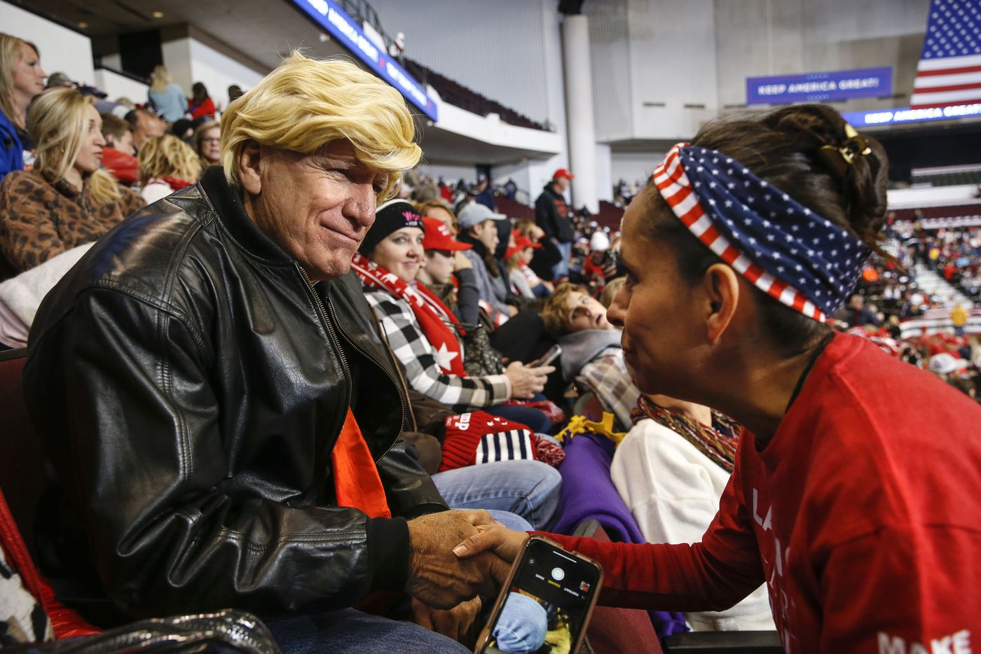 Martha Doss salue Eddie Barnes de Haughton, en Louisiane, vêtue d'une perruque Trump lors d'un rassemblement pour réélire le président Donald Trump à Bossier City.