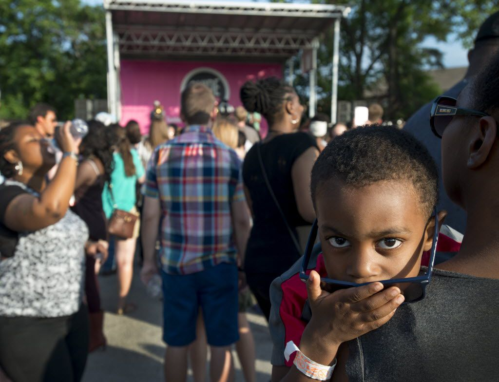 Four-year-old Caden Price listens to the Rebirth Brass Band in the arms of his mother, Alisha Adams. (Robert W. Hart/Special Contributor)
