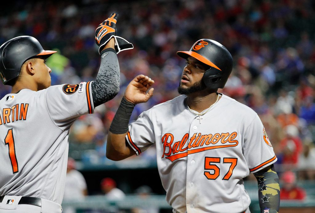 Baltimore Orioles' Richie Martin (1) and Hanser Alberto (57) celebrate after Alberto scored on a Chris Davis double in the sixth inning of a baseball game against the Texas Rangers in Arlington, Texas, Thursday, June 6, 2019. (AP Photo/Tony Gutierrez)