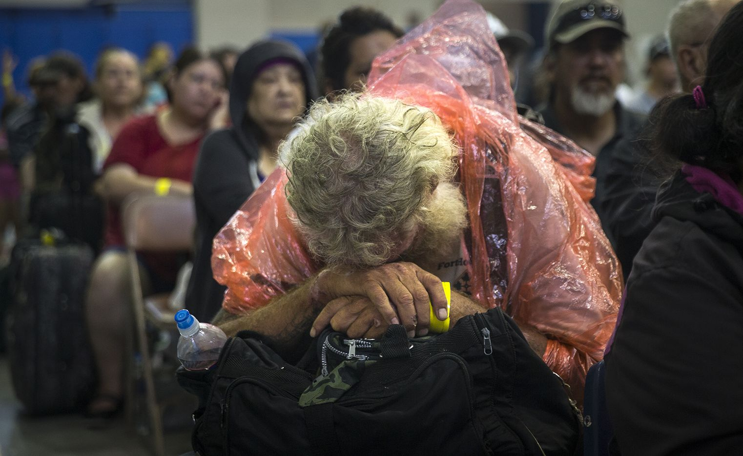 A man rests while waiting to board a bus headed for San Antonio at an evacuation center in Corpus Christi, Texas on Friday, Aug. 25, 2017. Hundreds of residents of the Corpus Christi area boarded buses Friday to be transported to a shelter in San Antonio as Hurricane Harvey is expected to make landfall on the Texas coast Friday night or early Saturday morning.
