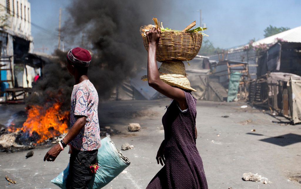 Street vendors walk past burning tires set up by anti-government protesters during a general strike in Port-au-Prince, Haiti, on July 9, 2018. A nationwide strike and protest was called to demand the resignation of Haiti's President Jovenel Moise after his government agreed to reduce subsidies for fuel as part of an assistance package with the International Monetary Fund. The fuel hike was suspended after widespread, violent protests broke out on Friday and over the weekend.