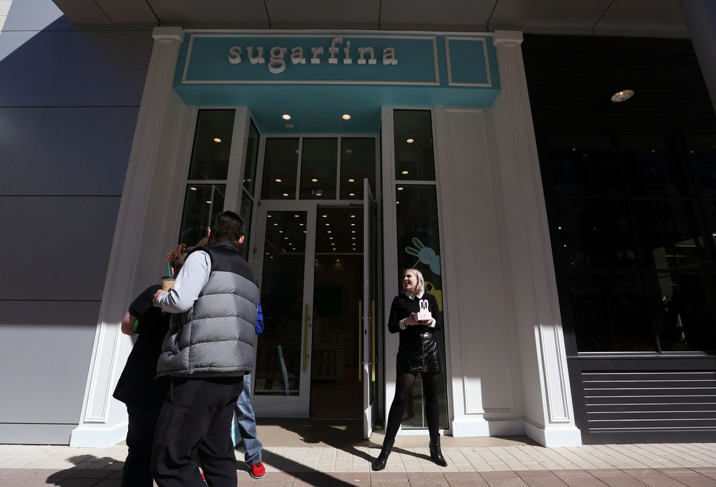 Allison Stewart (far right), boutique manager at Sugarfina, passes out candy samples to people walking by outside the shop at Legacy West.