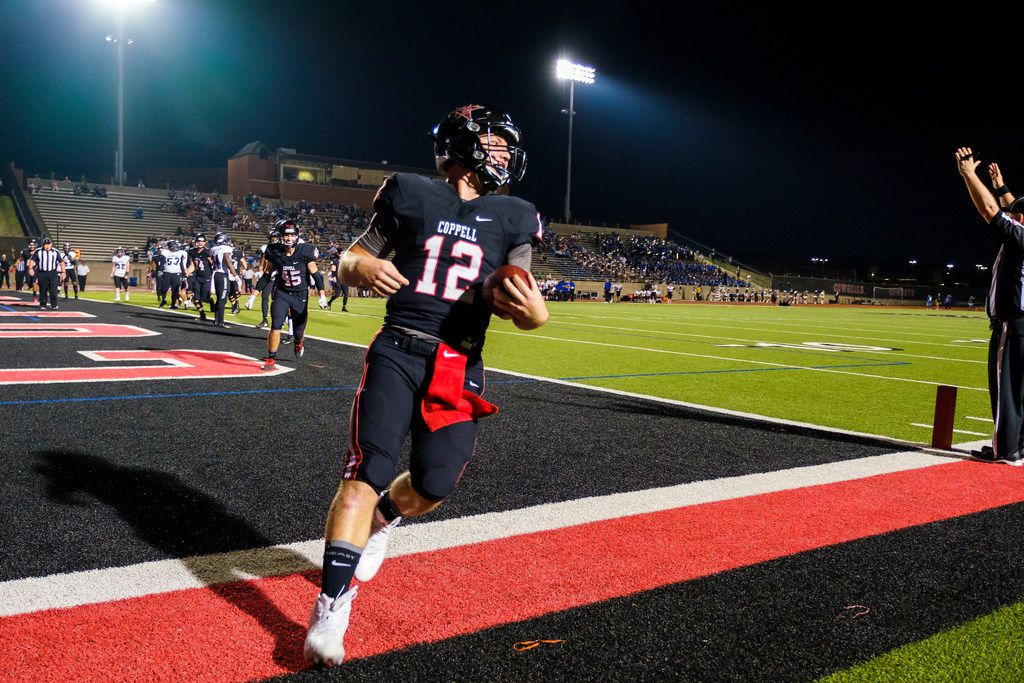 Coppell quarterback  Kevin Shuman (12) celebrates after scoring on a touchdown run during the first half of a high school football game against Hebron on Friday, Oct. 4, 2019, in Coppell, Texas. (Smiley N. Pool/The Dallas Morning News)
