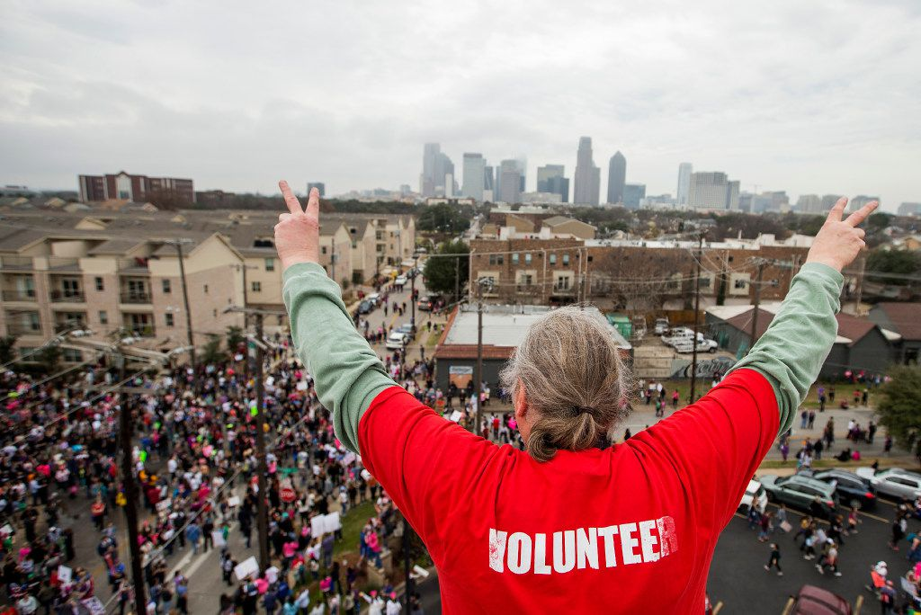Herb Keener waves to participants reaching the end of the Dallas Women's March from atop the roof of the at the Communications Workers of America Hall.