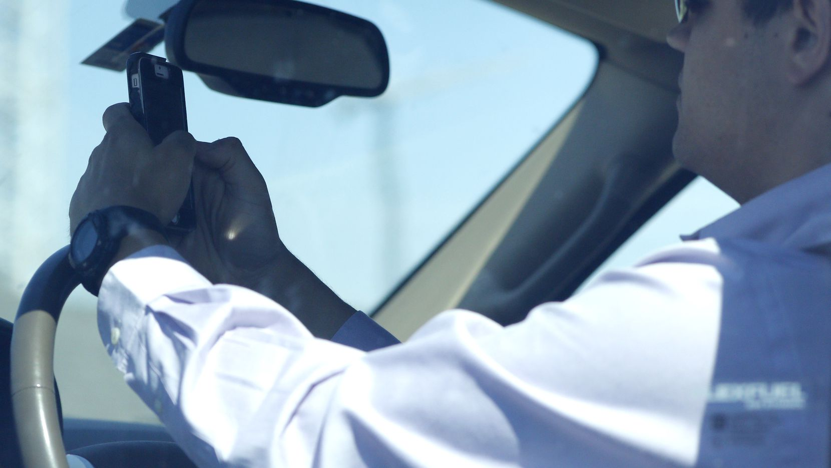 A man looks at his phone while driving down Woodall Rodgers Freeway in Dallas on July 16, 2015.