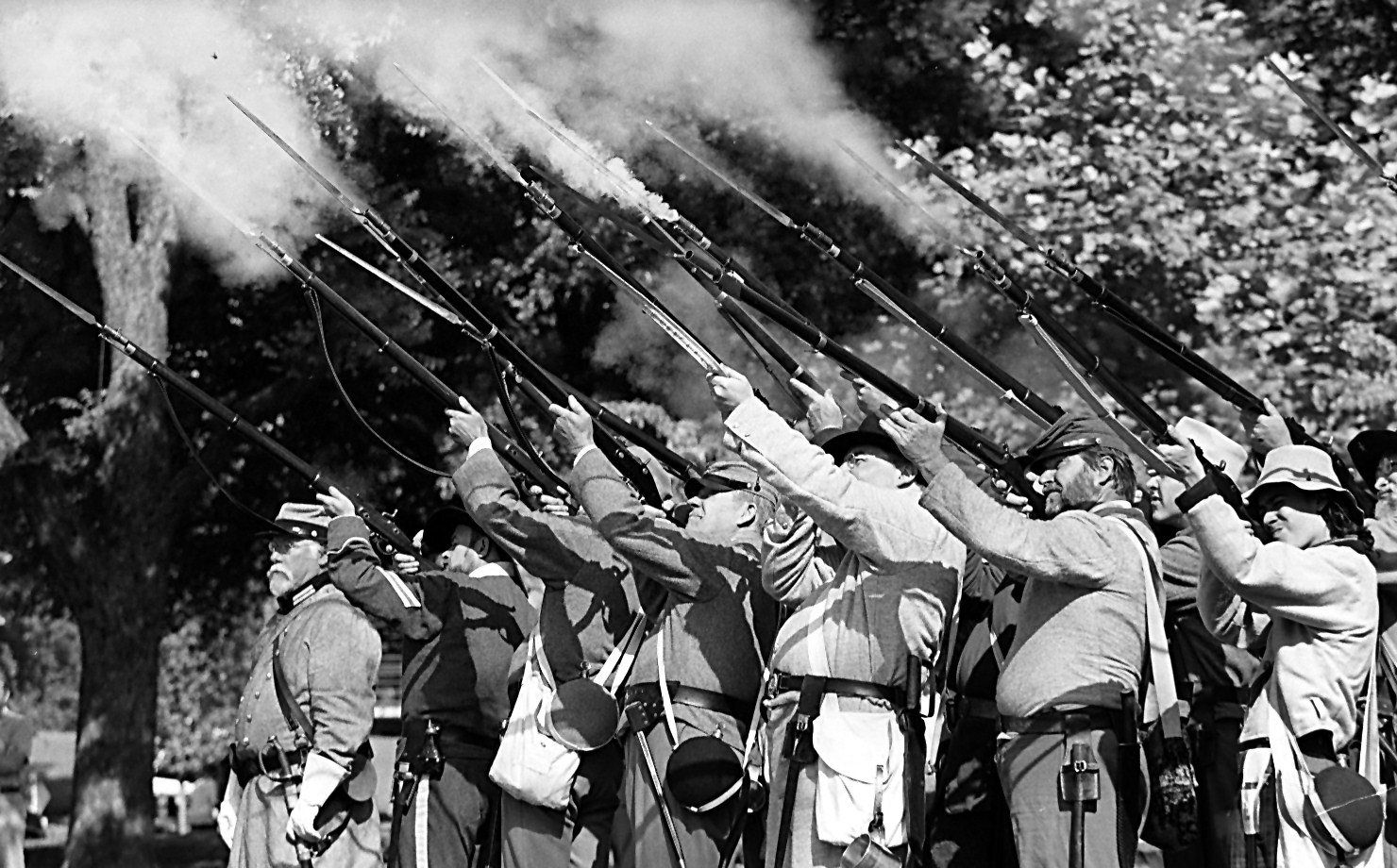 Re-enactors fire their guns to  honor and salute Confederate heroes at the third annual Confederate Heritage Day at Lee Park on May 20, 1995.