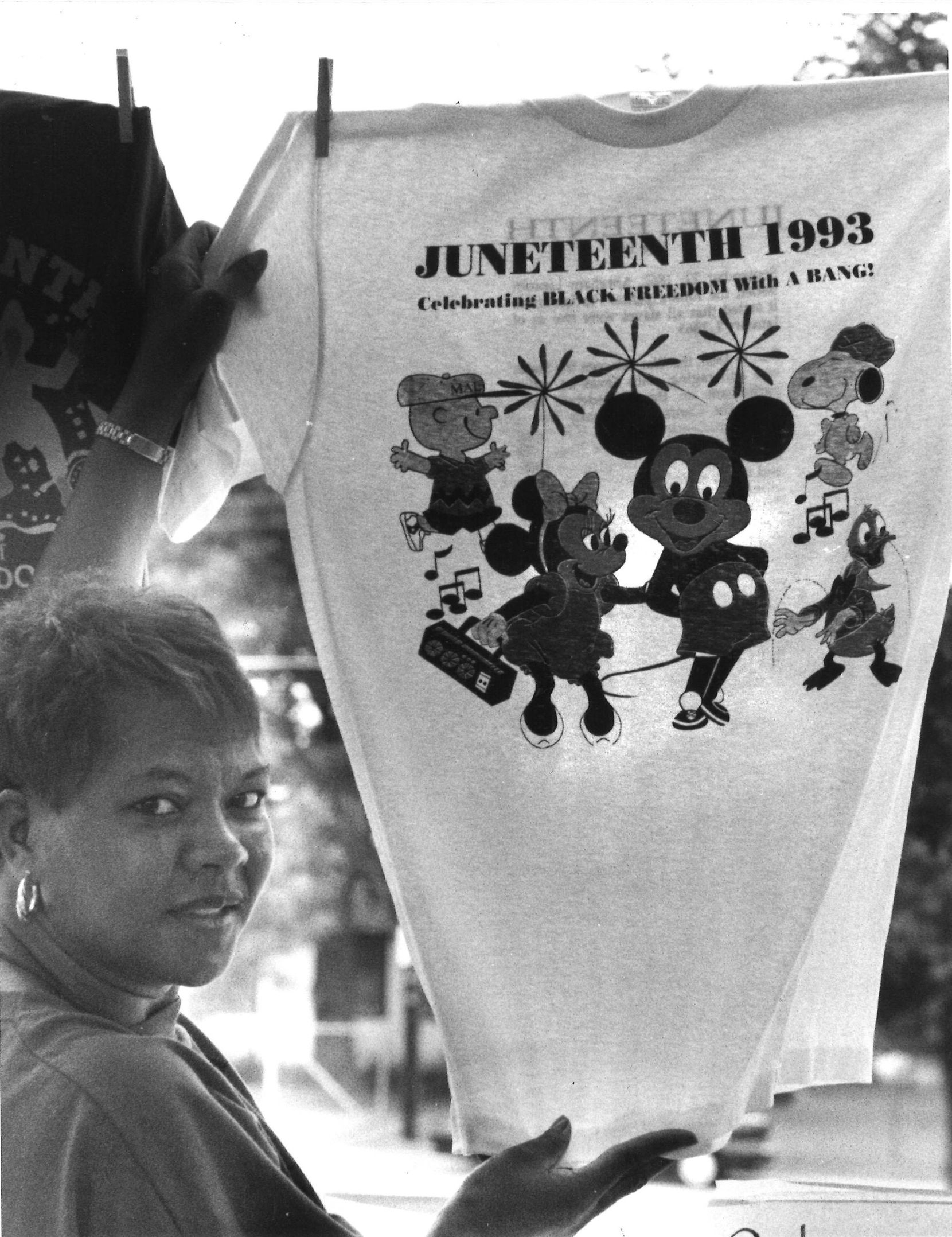 Pat Monroe, a Douglass Community Center volunteer, displayed a T-shirt offered for sale during the Juneteenth celebration in 1993,  which included a parade.