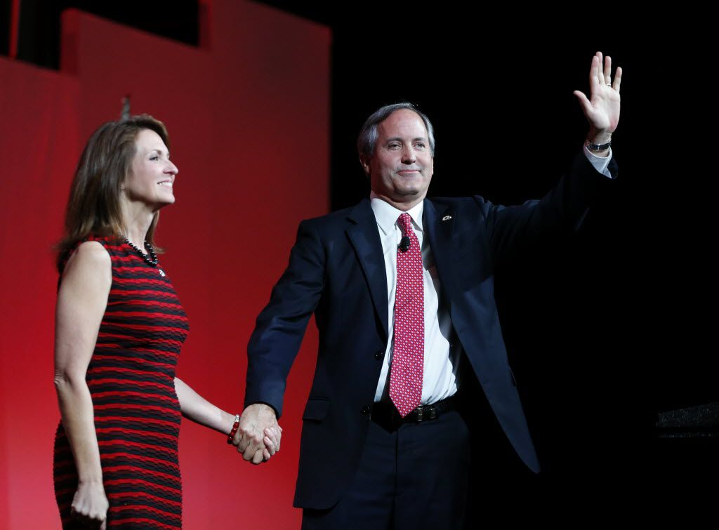 Texas Attorney General Ken Paxton waves to the crowd next to his wife, Angela Paxton, during the 2016 Texas Republican Convention at the Kay Bailey Hutchison Convention Center in Dallas on May 14, 2016.