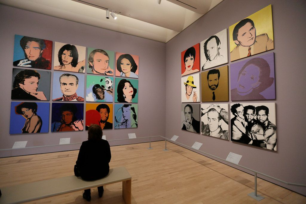 A woman views commissioned portraits created by Andy Warhol from 1968 to 1987 at the San Francisco exhibition.
