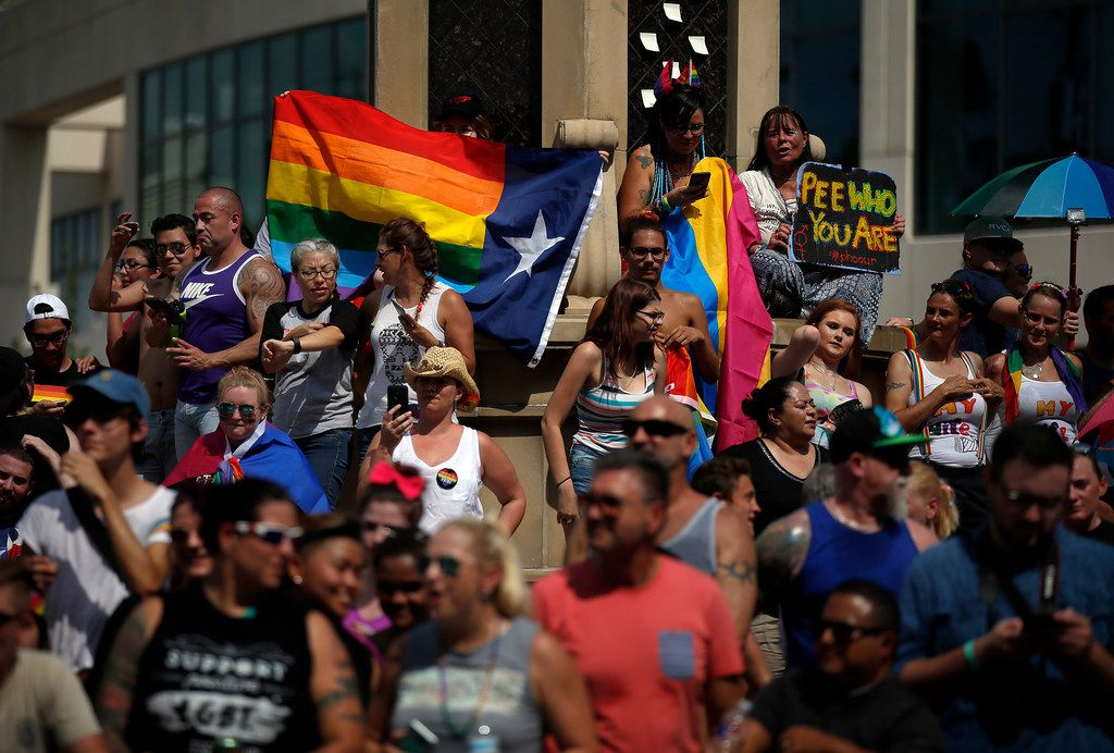 People view the 2017 Texas Freedom Parade from the Legacy of Love monument at Cedar Springs Rd. and Oak Lawn in Dallas.